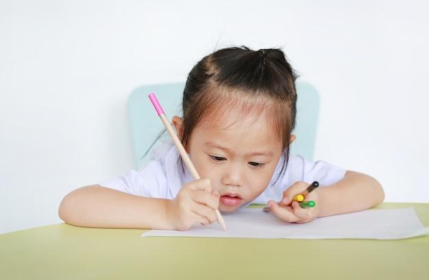 Aziatisch kind in school eenvormig met potlood die op lijst schrijven die op witte achtergrond wordt geïsoleerd.