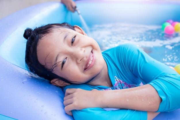Aziatisch kind meisje met plezier in tuin peuterbad met vader vullen wather op achtergrond.
