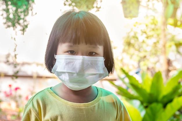 Aziatisch kind met het masker om zichzelf te beschermen tegen virussen en de verspreiding van het coronavirus te verminderen