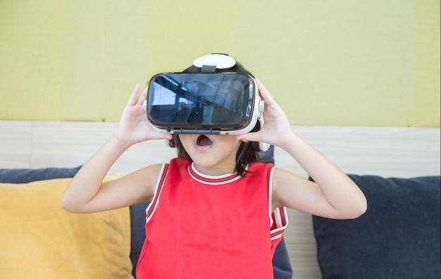 Aziatisch kind speelt vr-glastechnologie thuis op de woonkamer