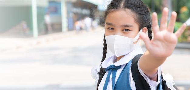 Aziatisch kindermeisje draagt masker om stof en luchtverontreiniging pm 2,5 te beschermen
