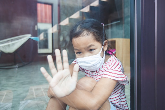 Aziatisch kindmeisje dat beschermingsmasker draagt dat door het venster naar buiten kijkt en thuis quarantaine van het coronavirus covid-19 en luchtverontreiniging pm2.5 blijft.