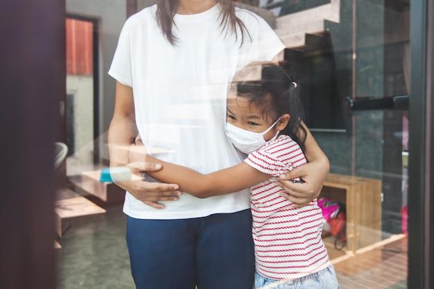 Aziatisch kindmeisje dat beschermingsmasker draagt dat haar moeder koestert en thuis quarantaine van het coronavirus covid-19 en luchtvervuiling pm2.5 blijft.