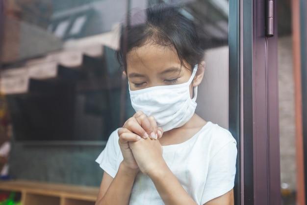 Aziatisch kindmeisje dat beschermingsmasker draagt dat voor een nieuwe dagvrijheid bidt om coronavirus covid-19 en thuis quarantaine van het coronavirus covid-19 en luchtvervuiling pm2.5 te blijven.