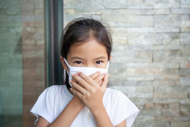Aziatisch kindmeisje dat een beschermingsmasker draagt ter bescherming van het coronavirus covid-19 en luchtsmogverontreiniging met pm 2,5. anti smog en virussen. luchtverontreiniging en medisch concept.