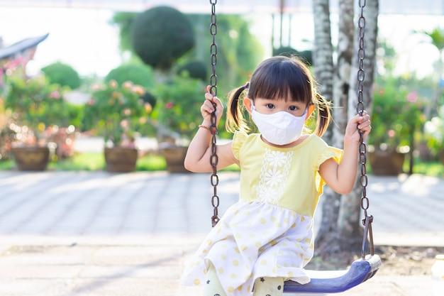 Aziatisch kindmeisje dat een stofgezichtsmasker draagt wanneer zij een stuk speelgoed bij de speelplaats speelt.