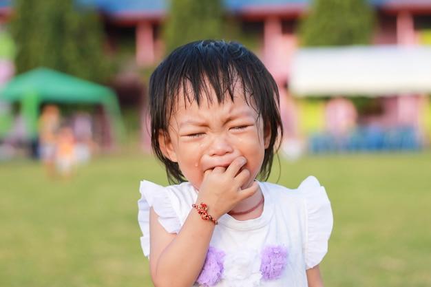 Aziatisch kindmeisje dat huilen wanneer zij met het stuk speelgoed op de speelplaats speelt.