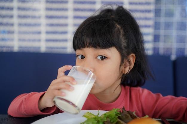 Aziatisch kindmeisje dat in de ochtend een glas melk drinkt. ontbijt tijd concept.
