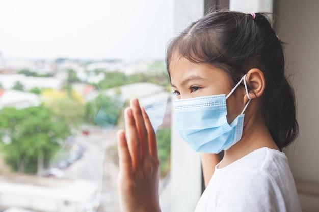 Aziatisch kindmeisje die beschermingsmasker dragen die buiten door het venster kijken en thuis blijven