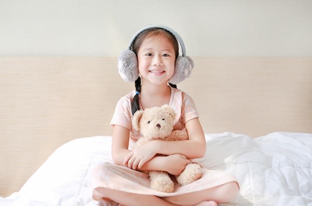 Aziatisch kindmeisje die de winteroorbeschermers dragen en teddybeer omhelzen