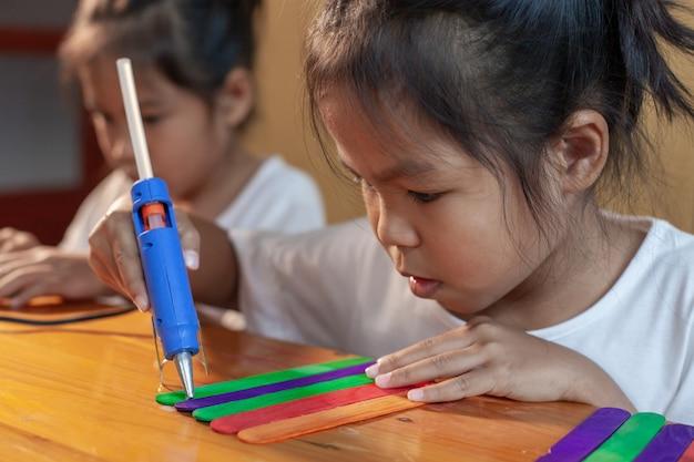 Aziatisch kindmeisje die gekleurde roomijsstokken lijmen door heet lijmpistool. kinderen hebben plezier om huis te maken in een handwerkproject.