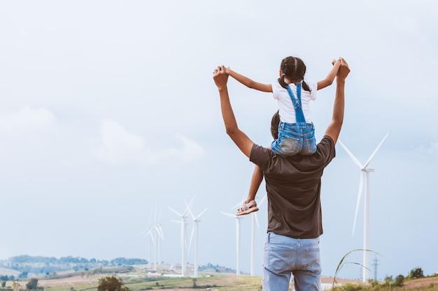 Aziatisch kindmeisje die op de schouders van de vader op het gebied van de windturbine berijden