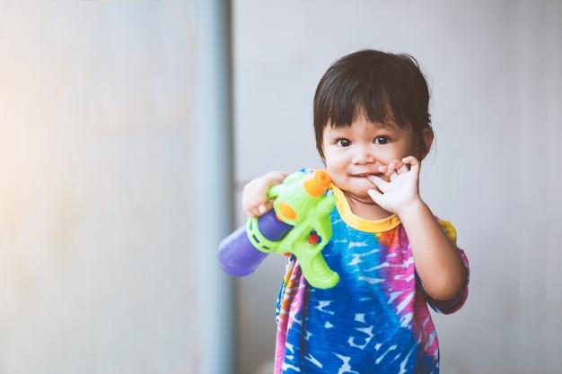 Aziatisch kindmeisje die pret hebben om water met waterkanon in songkran-festival thailand te spelen