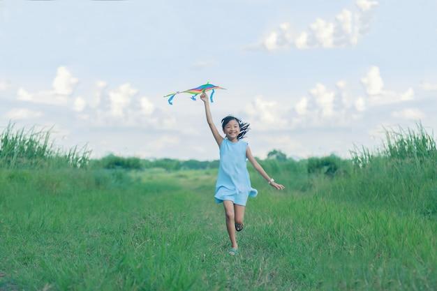 Aziatisch kindmeisje met een vlieger die en gelukkig op weide in de zomer in aard lopen