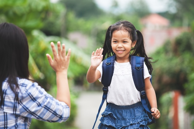Aziatisch kindmeisje met schooltas en haar moeder die hallo vijf gebaar maken vóór