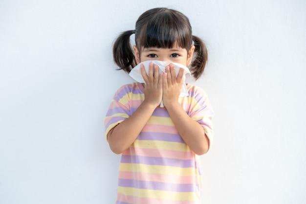 Aziatisch kindmeisje ziek met niezen op de neus en koude hoest op papieren zakdoekje omdat zwak of virus en bacteriën van stofweer en kleuterschool en kleuterschool