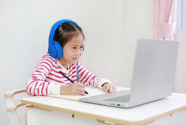 Aziatisch klein kind dat en hoofdtelefoonstudie online met laptop schrijft
