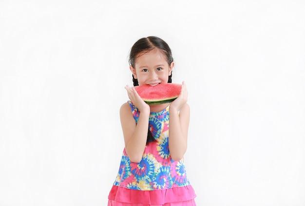 Aziatisch klein kind dat watermeloen eet dat op witte muur wordt geïsoleerd