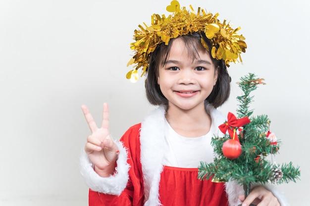 Aziatisch klein kindermeisje dat een rood kerstmanpak draagt om kerstvakantie thuis te vieren