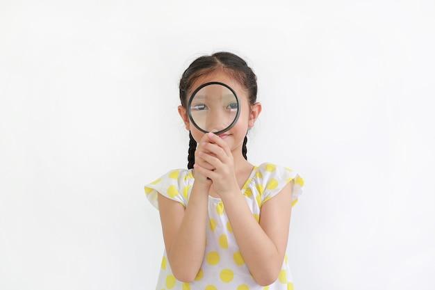 Aziatisch klein kindmeisje dat door een vergrootglas over witte achtergrond kijkt