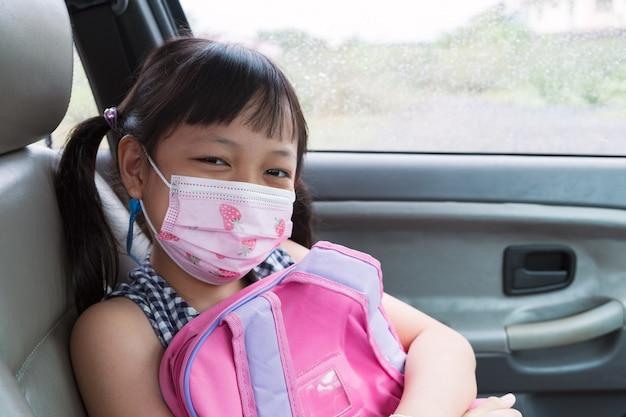 Aziatisch klein kindmeisje dat maskerzitting in de auto draagt