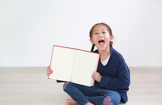Aziatisch klein kindmeisje dat met open boek lacht toont lege pagina. kind zit in de kamer en houdt een boek vast.