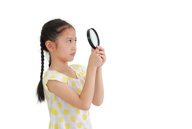 Aziatisch klein kindmeisje dat omhoog door een vergrootglas kijkt dat op witte achtergrond wordt geïsoleerd