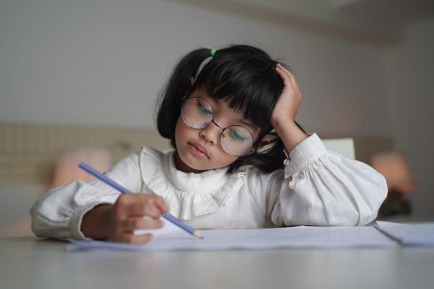 Aziatisch klein kindmeisje dat oogglazen draagt, doet thuis het werk.