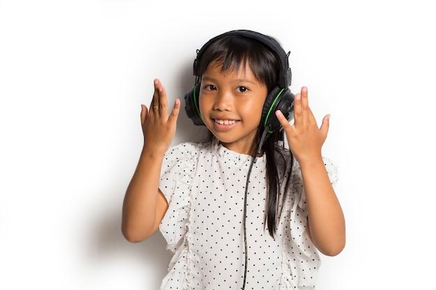 Aziatisch klein kindmeisje dat van muziek geniet. dansen en bewegen die echte positieve emoties uitdrukken