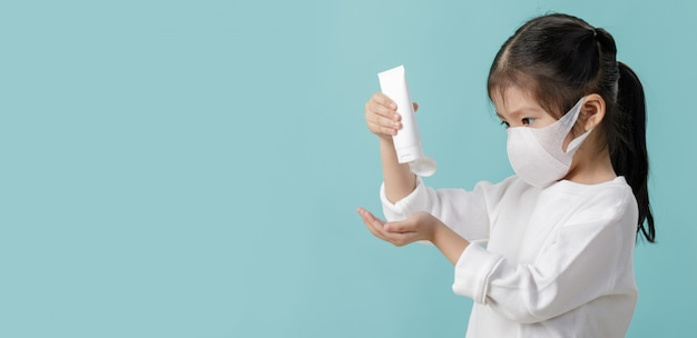 Aziatisch klein kindmeisje die masker dragen om coronavirusuitbraak te beschermen en handen wassen met alcoholgel, nieuw virus covid-19
