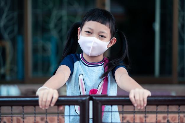 Aziatisch klein kindmeisje draagt een masker om coronavirus te beschermen ter ondersteuning van de strijd tegen de epidemie van de ziekte covid 19 thuis