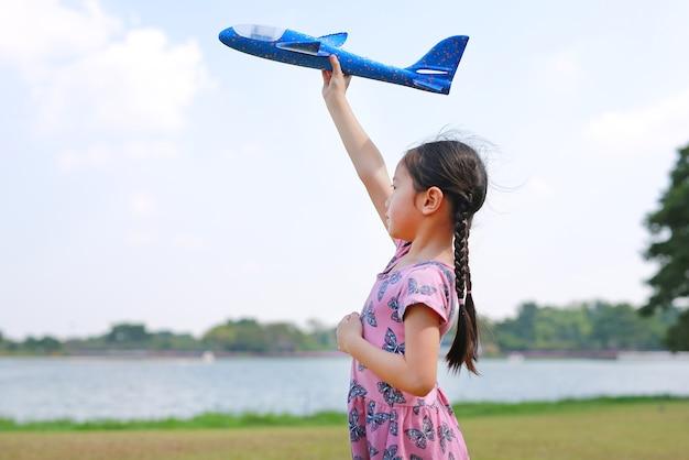 Aziatisch klein kindmeisje heft een blauw stuk speelgoed vliegtuig op dat op lucht in de natuurtuin vliegt.