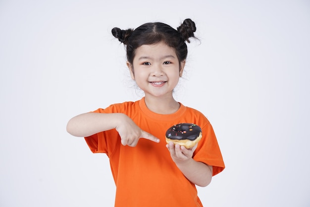 Aziatisch klein leuk meisje dat grote doughnut eet die op wit wordt geïsoleerd