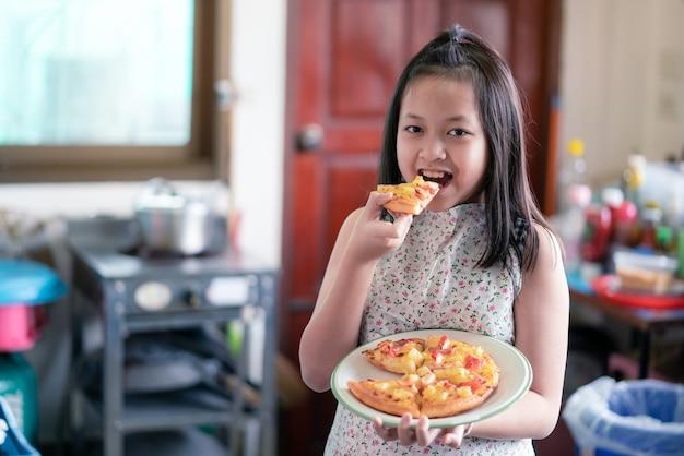 Aziatisch klein meisje bereidt en eet zelfgemaakte pizza in de huiskeuken met een glimlach en gelukkig