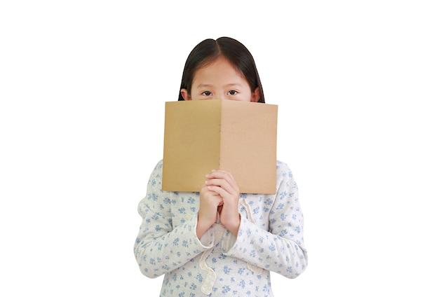Aziatisch klein meisje dat bruine boekomslag vasthoudt, verbergt haar mond en neus met het kijken naar camera geïsoleerd op een witte achtergrond. afbeelding met uitknippad
