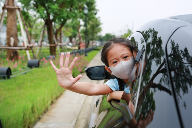 Aziatisch klein meisje dat een hygiënisch gezichtsmasker draagt, steekt haar hoofd uit het autoraam met een gebaar van een stopteken van de hand