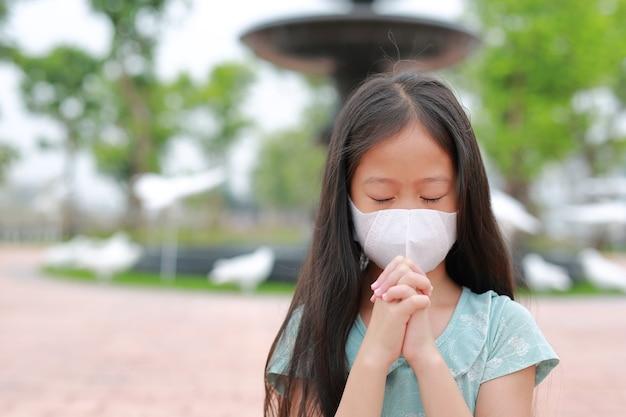 Aziatisch klein meisje dat gezichtsmasker draagt en bidt om covid-19 te stoppen tijdens de uitbraak van het coronavirus