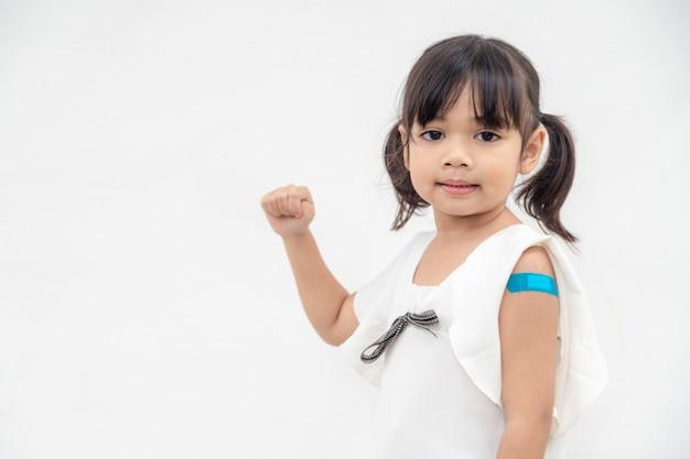 Aziatisch klein meisje dat zijn arm laat zien na vaccinatie of vaccinatie van kinderen