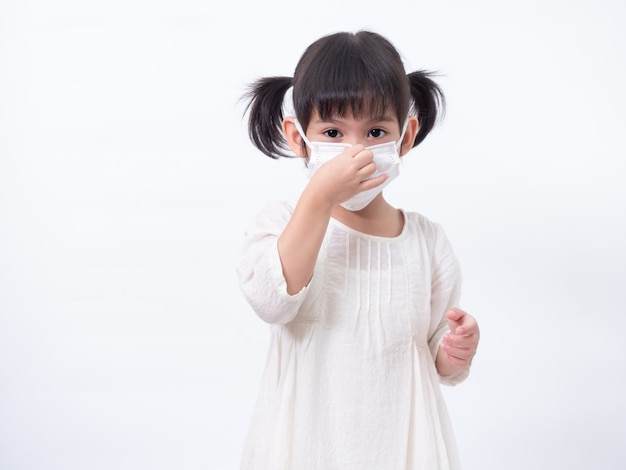 Aziatisch klein schattig meisje van 4 jaar oud draagt een hygiënisch gezichtsmasker om het coronavirus covid-19 koude griep of vervuiling op de witte muur te beschermen