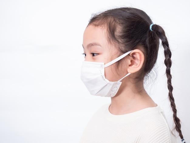Aziatisch klein schattig meisje van 6 jaar oud draagt een hygiënisch gezichtsmasker om het coronavirus covid-19 koude griep of vervuiling op de witte muur te beschermen