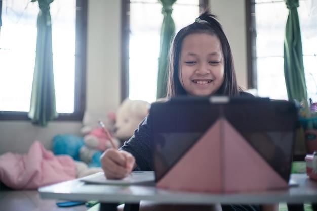 Aziatisch klein schoolmeisje dat tijdens haar online les thuis studeert met een glimlach en gelukkige, sociale afstand tijdens quarantaine, online onderwijsconcept