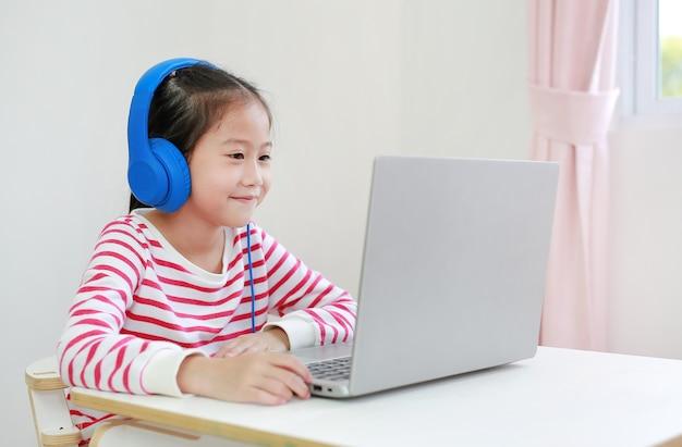 Aziatisch klein schoolmeisje die online het leren van de hoofdtelefoonstudie gebruiken