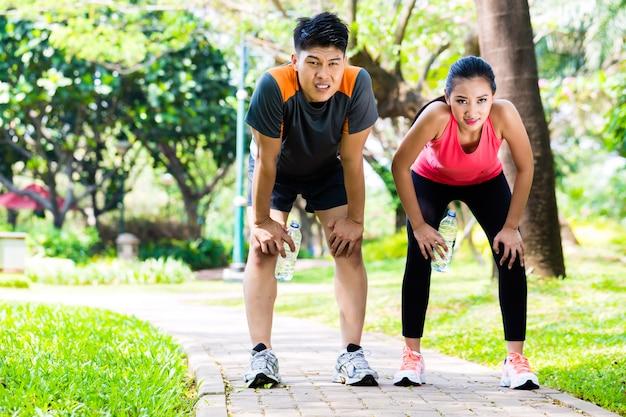 Aziatisch koppel neemt ademloze pauze van hardlopen