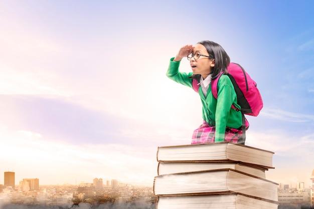 Aziatisch leuk meisje met glazen en rugzakzitting op de stapel van boeken met stad en blauwe hemel