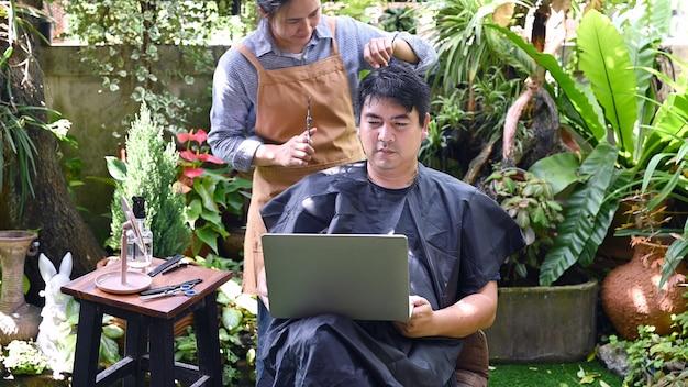 Aziatisch liefdespaar dat een kapsel maakt om zijn uiterlijk thuis op te frissen. werk vanuit huis en salon in de tuin.