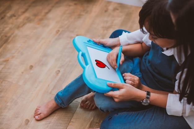 Aziatisch mamma die leuke jongen onderwijzen aan het trekken van rood hart in raad met kleurenpen