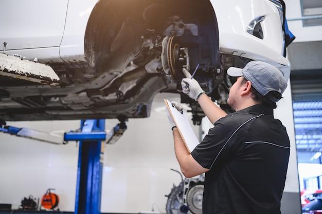 Aziatisch mannelijk autotechnicus auto-onderhoud voor klanten volgens gespecificeerd voertuig