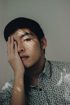 Aziatisch mannetje dat een knoop-omhooggaand overhemd draagt dat zijn oog behandelt met zijn hand