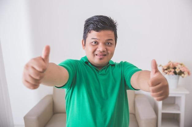 Aziatisch mannetje dat en duim glimlacht toont