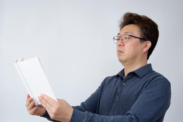 Aziatisch mannetje dat iets in zijn boek probeert te lezen. slecht zicht, presbyopie, bijziendheid.